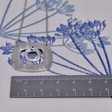 Square textured silver pendant necklace with charm by Article Jewellery