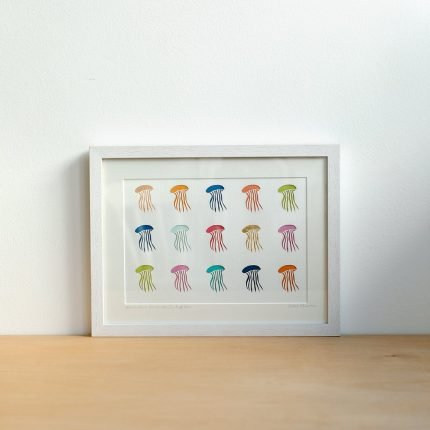 Framed artwork featuring a rows of brightly coloured paper cut jellyfish by Cornish Paper Cut Art