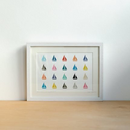 Framed artwork featuring a rows of brightly coloured paper cut boats by Cornish Paper Cut Art