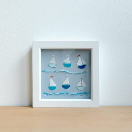 Small framed picture of boats made from beach find plastic by Smartie Lids on the Beach