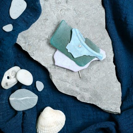Statement brooch made from riveted layers of beach plastic by Sarah Drew