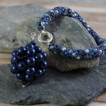 Beaded bracelet in blue tones made from Swarovski pearls closed with a sterling silver clasp by Article Jewellery with beaded long length midnight blue pendant