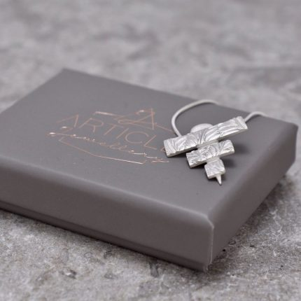 Silver pendant necklace in the shape of a triangle made from three strips by Article Jewellery with box