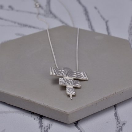 Silver pendant necklace in the shape of a triangle made from three strips by Article Jewellery