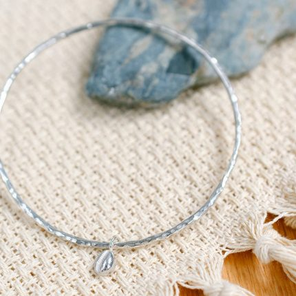 Sterling silver bangle with cowrie shell charm by Porth Jewellery