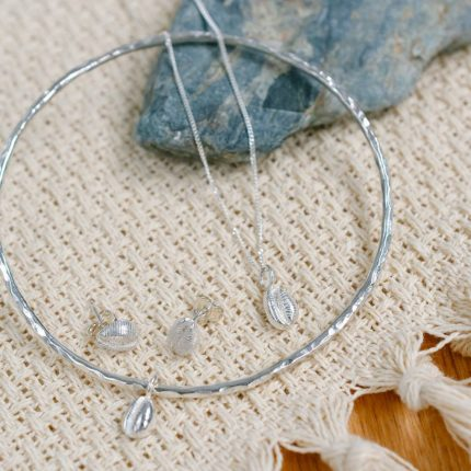 Bangle, pendant and stud earring set of sterling silver cowrie shells by Porth Jewellery