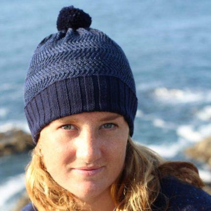 Model wearing Navy Bobble Hat by Cornish Knitwear designer Jessye Boulton