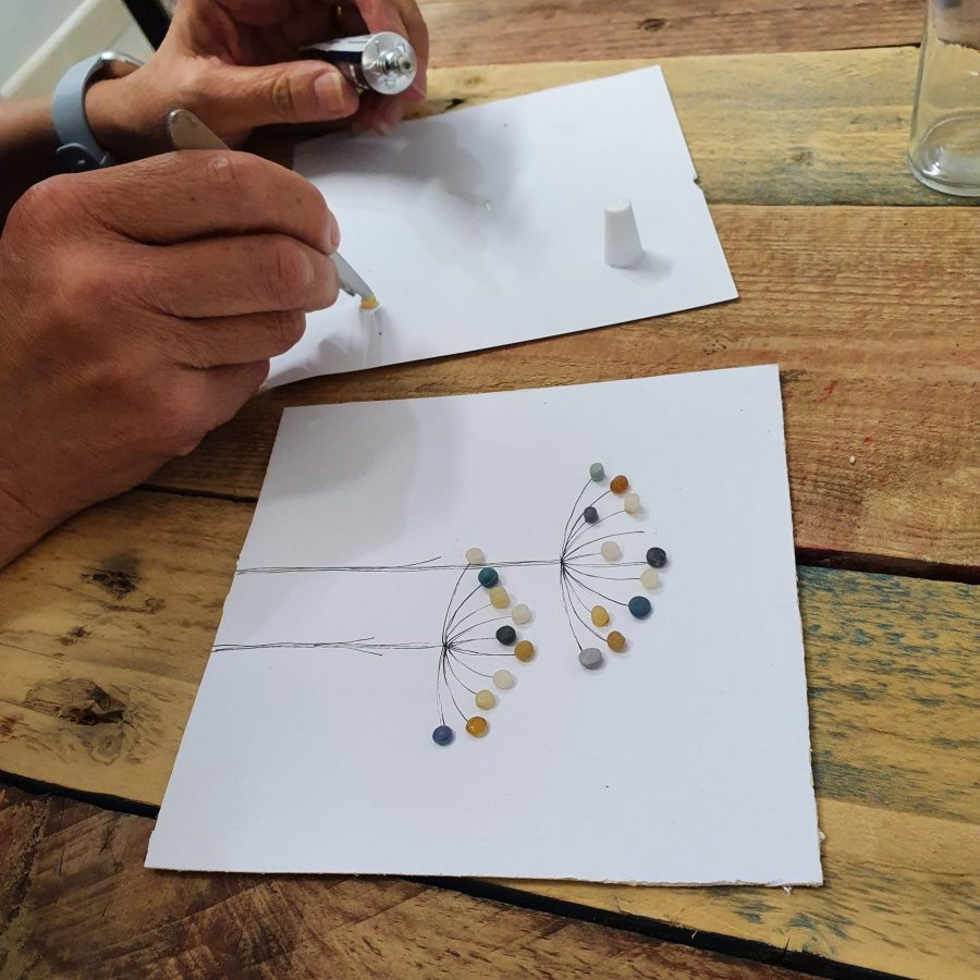 Close up of someone making nurdle seeded art at a workshop held by Michelle Costello from Smartie Lids on the Beach