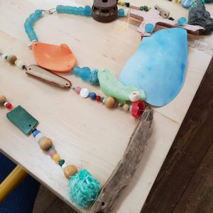 Examples of unique necklaces made from found materials at a workshop with Sarah Drew